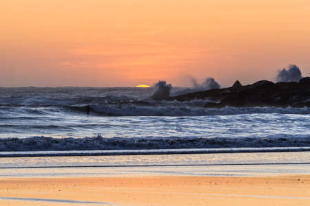 Glowing orange sun setting behind the horizon adding an orange glow to the sky and a reflection on the wet sand in Hunters Cove a popular surfing spot in the Oregon coast Stok Fotoğraf