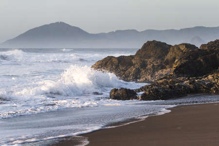 Rocky shoreline in Nesika Beach, Oregon late in the afternoon with the sun approaching the horizon and the waves crashing into the rocks Stok Fotoğraf