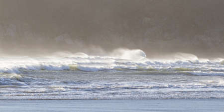 a windy day at the coast with a spray or mist  blowing from the top of the waves as the strong sunlight lights the scene from the back
