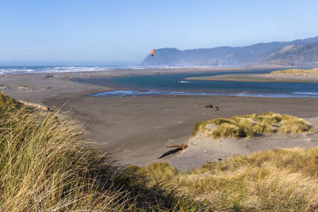 Man kite surfing in the mouth of the Pistol River with a rugged coast in the background characteristic of southern Oregon