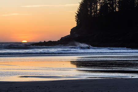 Man in the cold coastal waters of the Oregon coast surfing as the sun sets adding an orange glow on the horizon