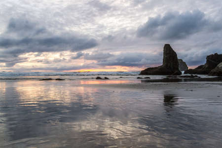 end of the day at the beach a bit of color in the dark clouds and the prominent rock features characteristic Face Rock State Park, Bandon Oregon Stok Fotoğraf