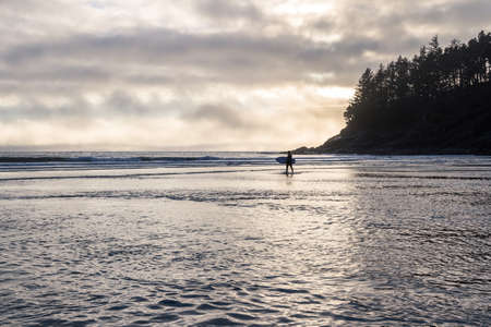 Man walking out of the ocean onto the beach holding his surf board with golden light from the clouds reflecting on the water