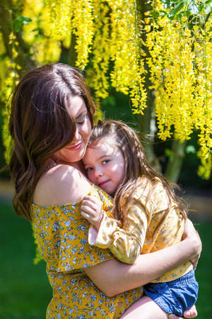Mother and daughter with matching outfits with yellow flowers in the background