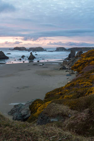 end of the day at the beach a bit of color in the dark clouds and the prominent rock features characteristic Face Rock State Park, Bandon Oregon Foto de archivo