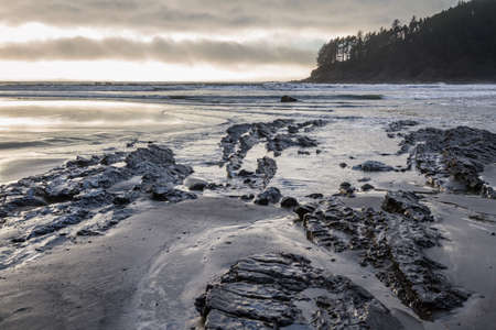 moody afternoon at the Oregon coast with low clouds and a bit of light on the rocky shoreline leading to the point at Cape Sebastian in southern Oregon Stok Fotoğraf - 152842433