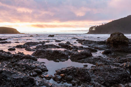 Colorful clouds reflecting on the water at low tide viewed from Hunters Cove in the southern Oregon coast Stok Fotoğraf - 152842434