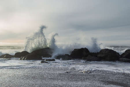 Rocky shoreline in Nesika Beach, Oregon late in the afternoon with the sun approaching the horizon and the waves crashing into the rocks Stok Fotoğraf - 152842435