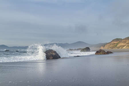 Rocky shoreline in Nesika Beach, Oregon late in the afternoon with the sun approaching the horizon and the waves moving with the changing tides Stok Fotoğraf - 152842316