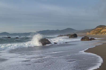 Rocky shoreline in Nesika Beach, Oregon late in the afternoon with the sun approaching the horizon and the waves moving with the changing tides Foto de archivo