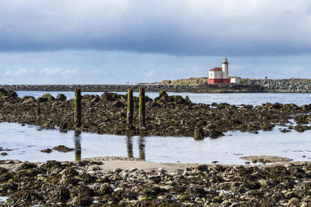 Coquille River Lighthouse in Bandon Oregon on a cloudy and foggy day typical of winter on the coast Stok Fotoğraf - 152842385