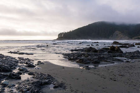 moody afternoon at the Oregon coast with low dense clouds with a bit light coming thru the lighter patches and reflecting on the water Stok Fotoğraf - 152842386