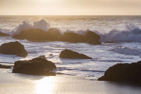 Rocky shoreline in Nesika Beach, Oregon late in the afternoon with the sun approaching the horizon and the waves crashing into the rocks Stok Fotoğraf - 152842387