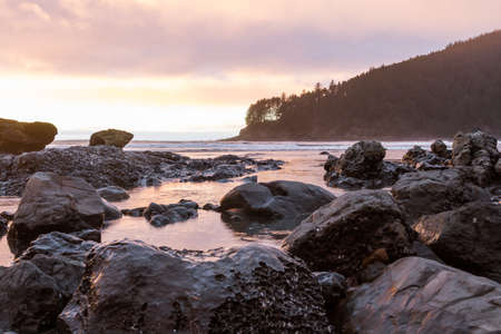 Colorful clouds reflecting on the water at low tide viewed from Hunters Cove in the southern Oregon coast