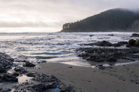 moody afternoon at the Oregon coast with low dense clouds with a bit light coming thru the lighter patches and reflecting on the water Stok Fotoğraf