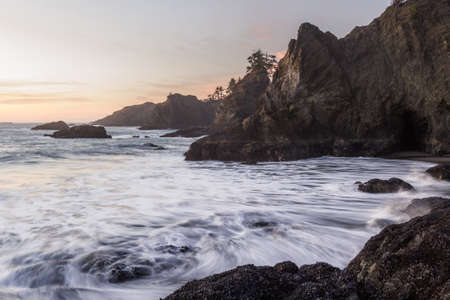 The sun sets on Secret Beach in the southern Oregon coast at sunset with its many Islets topped with evergreen trees and blurred waves moving in as the tides change Foto de archivo
