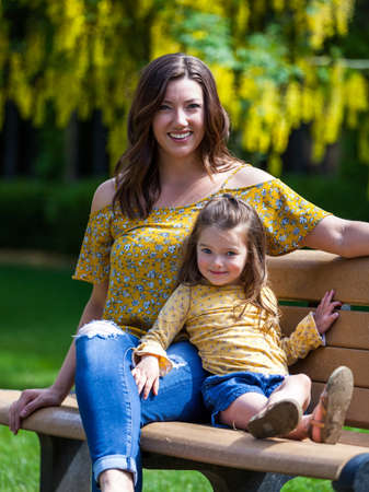 Mother and daughter with matching outfits sitting on a bench with yellow flowers in the background Stok Fotoğraf - 152842399