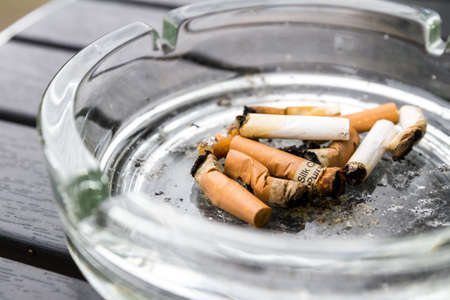 group of cigaret filters in a dirty clear glass ashtray after being burnt and smoked