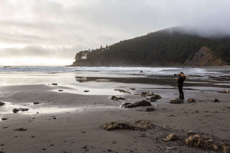 Woman with a large camera and a small chihuahua in her coat enjoying a beautiful afternoon in Hunters Cove in the southern Oregon coast Stok Fotoğraf