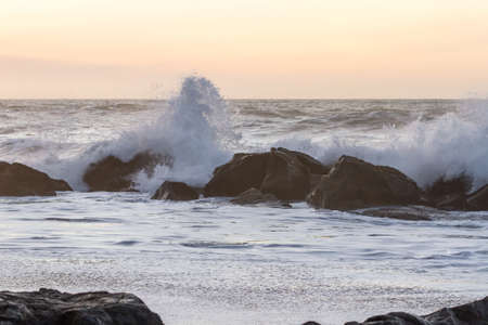 Rocky shoreline in Nesika Beach, Oregon late in the afternoon with the sun approaching the horizon and the waves crashing into the rocks Foto de archivo