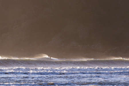 man surfing in a full dry suit in Hunters Cove, a popular surfing spot in the southern Oregon coast Stok Fotoğraf