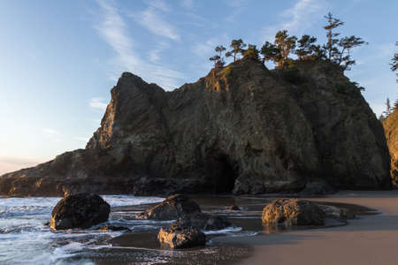 Tranquil beach in the southern Oregon coast known as Secret Beach with beautiful Islets topped with evergreen trees on a beautiful sunny day Stok Fotoğraf - 152842002