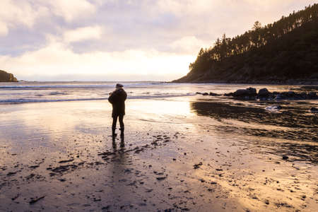 Woman enjoying a beautiful sunset from hunters cove with bright clouds reflecting on the wet sand Stok Fotoğraf