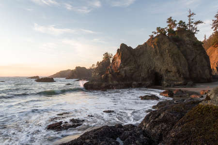 Beautiful sunset in Secret Beach Oregon with a soft warm glow on the rocks and evergreen trees on top of the islets that make this beach so recognizable. Stok Fotoğraf