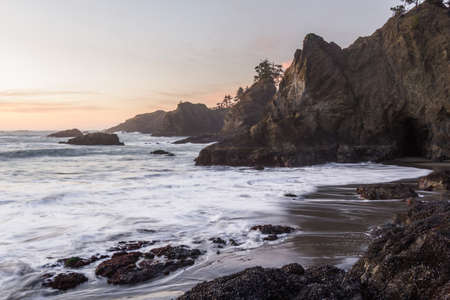 The sun sets on Secret Beach in the southern Oregon coast at sunset with its many Islets topped with evergreen trees and blurred waves moving in as the tides change Stok Fotoğraf