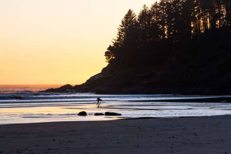 Man walking out of the cold waters of the Oregon coast with his surf board as the sun adds an orange glow across the horizon Stok Fotoğraf