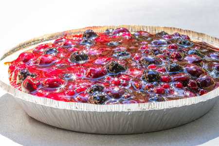 close up of a mixed berry pie under bright sunlight reflecting a beautiful sparkle on the shiny fruit