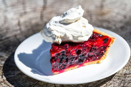 close up of a fresh summer berry pie made with huckleberries and blackberries with red gelatin on a graham cracker crust topped with whipped cream Stok Fotoğraf - 154166388