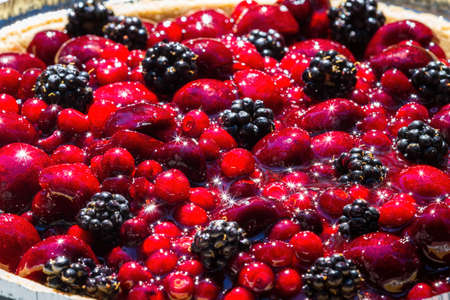 close up of a bowl of mixed berries under bright sunlight reflecting a beautiful sparkle on the shiny fruit