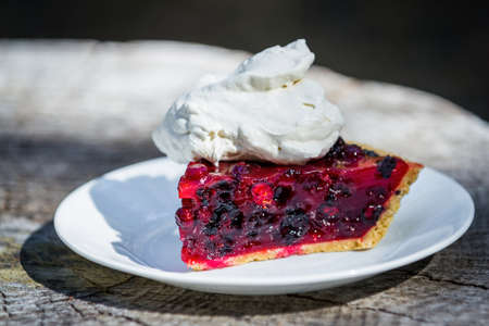 close up of a fresh summer berry pie made with huckleberries and blackberries with red gelatin on a graham cracker crust topped with whipped cream Stok Fotoğraf - 154166263