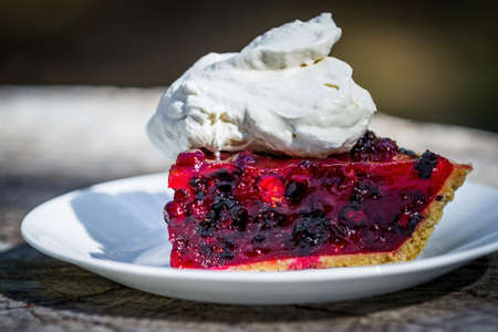 close up of a fresh summer berry pie made with huckleberries and blackberries with red gelatin on a graham cracker crust topped with whipped cream