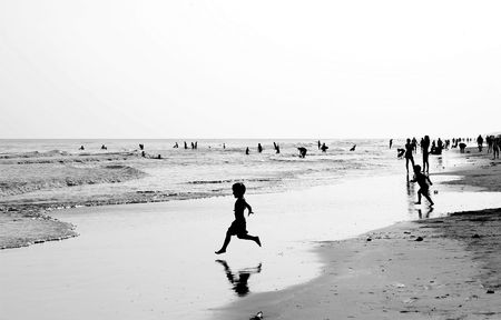 frolicking: Silhouette of children frolicking on a crowded beach in black and white