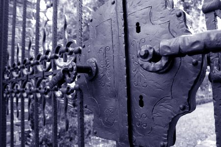 Blue tinted monochrome of an antique gate and lock