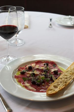 carpaccio with olives and a glass of red wine