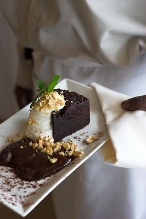 cocoa cake with nuts and mint being served by waiter photo