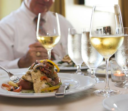 business dinner of flounder and white wine, focus on foreground Stock Photo - 2189330