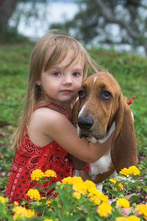 little girl hugging her basset hound, shallow focus portrait