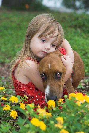 shallow: little girl hugging her basset hound, shallow focus portrait