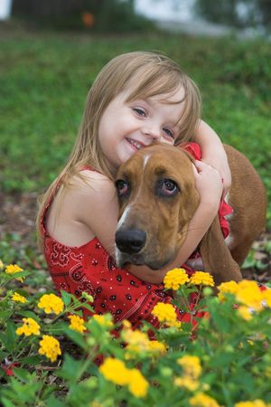 endure: little girl hugging her basset hound, shallow focus portrait