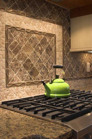 colorful tea kettle on stove with tile backsplash Stock Photo