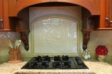 expensive granite: stove detail with ornamental tile backsplash Stock Photo