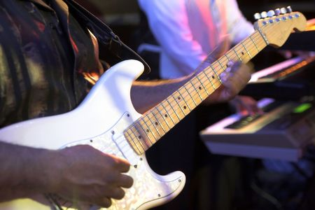 hands playing bass guitar with motion blur and keyboardist
