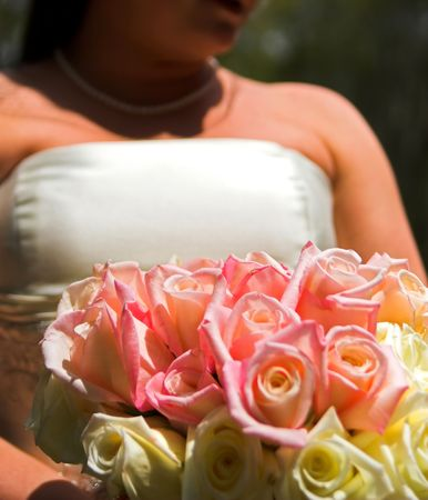 bride holding bouquet of roses, focus on foreground photo