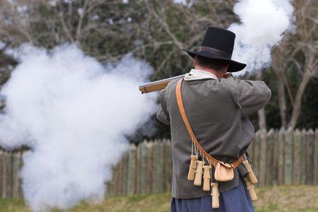 muzzleloader: man firing flint lock rifle