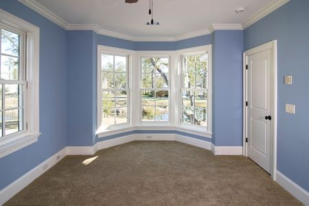 blue bedroom with lots of windows looking out onto pond Stock Photo