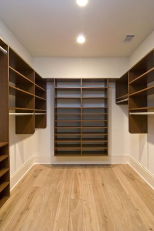 large empty walk-in closet with wood shelving photo